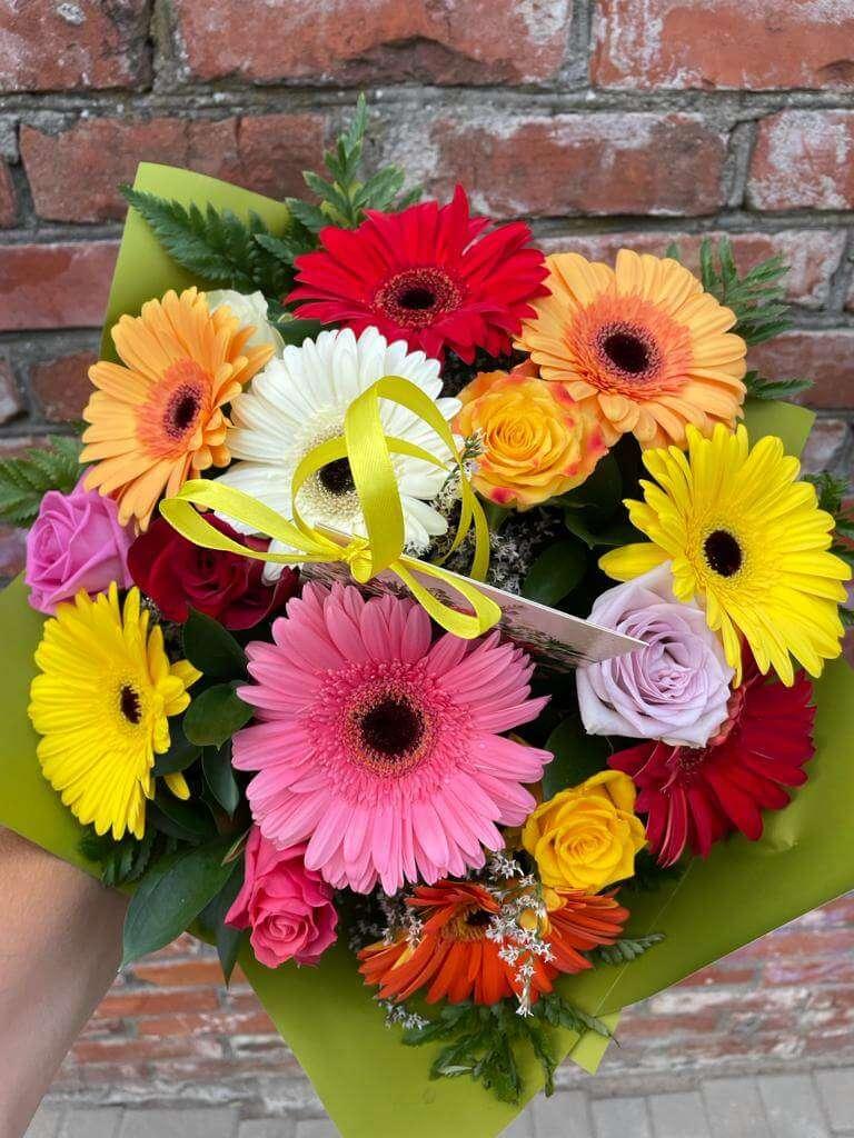 Spilgto krāsu gerberas un rozes pušķī un glītu iepakojumu